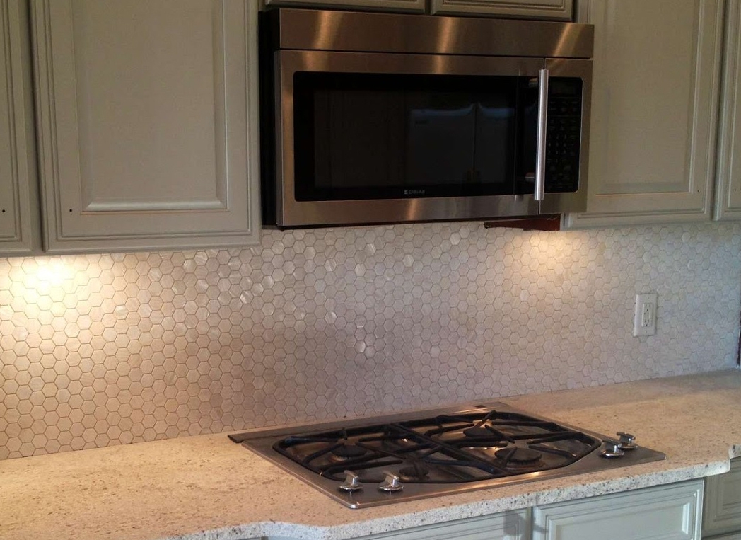 hexagonal white mosaic tile backsplash